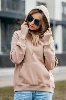 Fasion blondynka w brązowych okularach z kapturem oversize i makietą niebieskich dżinsów na logo lub projekt marki