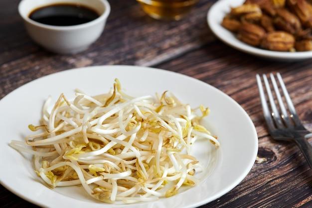 Fasola mung kiełkuje w talerzu. surowa zdrowa żywność ekologiczna. tradycyjne danie warzywne we wschodniej azji.