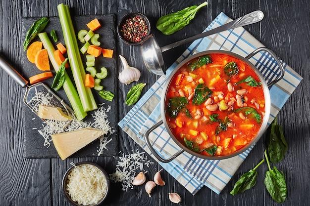 Fasola żurawinowa zupa z parmezanem szpinakowym i pomidorem w metalowym rondlu na czarnym drewnianym stole, składniki na czarnej kamiennej desce, kuchnia włoska, widok poziomy z góry, leżał płasko