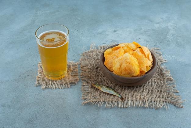 Fasolka po bretońsku, dushbara, łyżka, pieprz i sól na desce, na niebieskim stole.