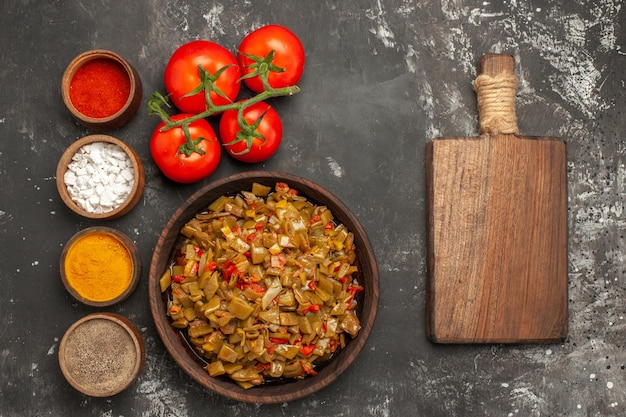 Fasolka szparagowa i przyprawy fasolka szparagowa w misce obok drewnianej deski do krojenia pomidorów i misek z przyprawami na ciemnym stole