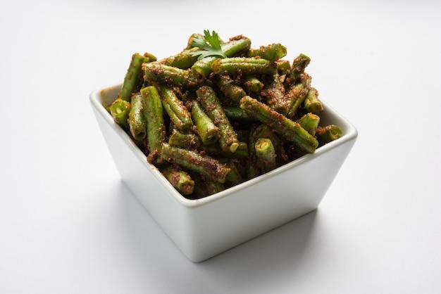 Fasolka szparagowa masala suche curry, indyjski przepis warzywny podawany w kwadratowej misce na kolorowym tle, selektywne skupienie