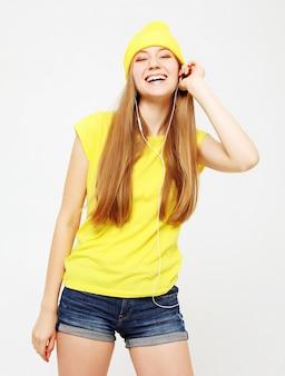 Fasonuj całkiem fajną dziewczynę w słuchawkach słuchających muzyki w żółtym kapeluszu i koszulce