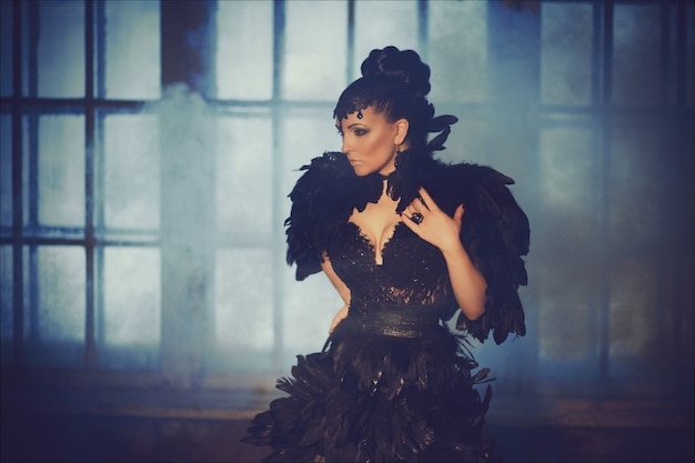 Fasonuj gotycki portret pięknej brunetki w długiej czarnej sukience z kruczych piór. halloween
