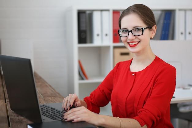 Fasonuje biznesowej kobiety w czerwonej koszula i szkła portrecie siedzi w biurze i pracuje na laptopie