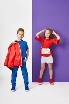 Fasonuje chłopiec i dziewczyny w eleganckich ubraniach na barwionym ściennym tle. jesienne jasne ubrania dla dzieci, dziecko pozuje na kolorowym fioletowym różowym tle.