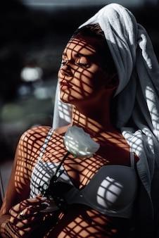 Fasonuje fotografię młoda piękna kobieta z zamkniętymi oczami i cieniami na jej twarzy. brunetka z ręcznikiem na głowie, w białej bieliźnie i białym kwiacie w dłoni, pozuje do kamery.