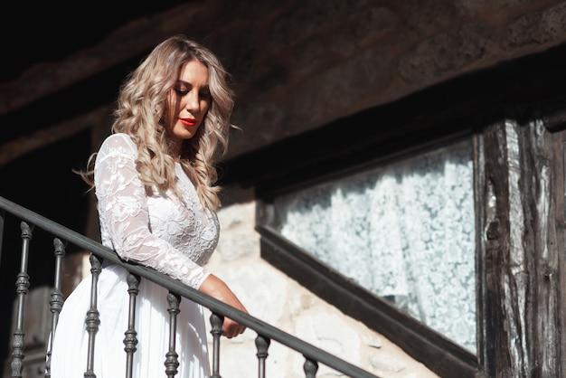 Fasonuje fotografię piękna kobieta w ślubnej sukni pozować plenerowy.