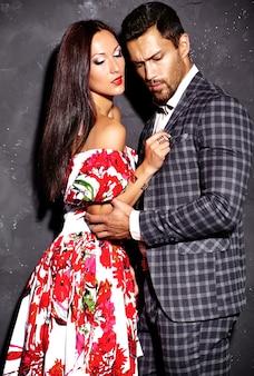 Fasonuje fotografię przystojny elegancki mężczyzna w kostiumu z piękną seksowną kobietą pozuje blisko szarości ściany