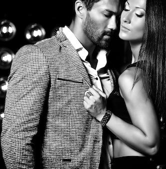 Fasonuje fotografię przystojny elegancki mężczyzna w kostiumu z piękną seksowną kobietą pozuje na czarnym studiu zaświeca tło