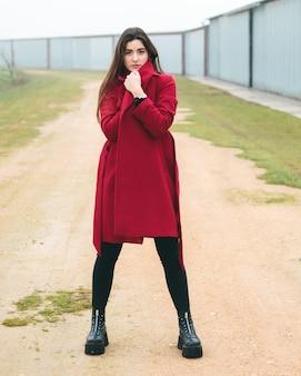 Fasonuje kobieta portret młoda ładna dziewczyna pozuje w wiejskiej scenie w europa. moda zimowa i wiosenna, ubrana w czerwoną kurtkę.
