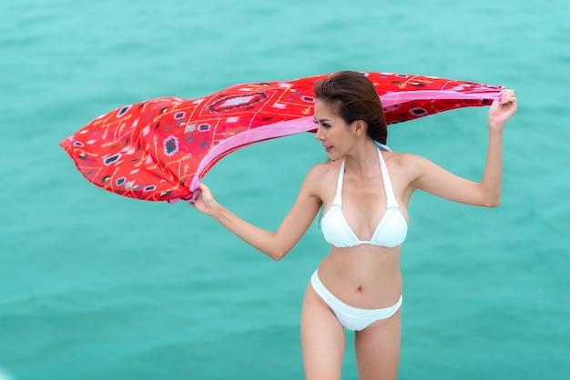Fasonuje lato plenerową fotografię seksowna dziewczyna z ciemnymi włosami w luksusowym bikini relaksuje na jachcie w morzu