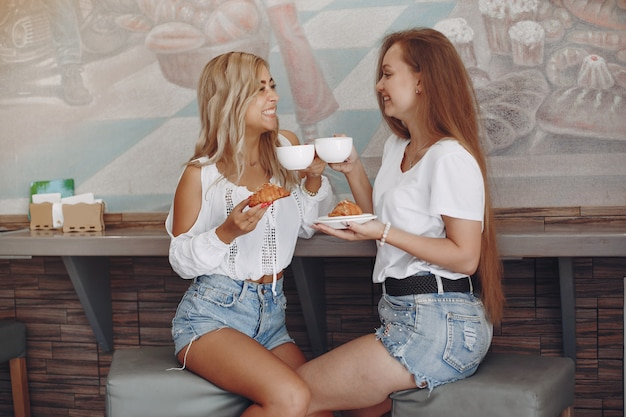 Fasonuje młode dziewczyny siedzi w kawiarni