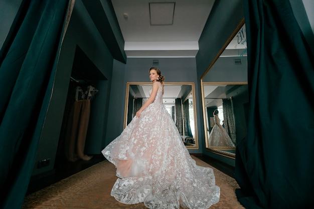 Fasonuje panny młodej w białej ślubnej sukni pozuje w przymierzalni.