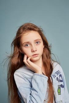 Fasonuje pięknej dziewczyny pozuje na błękitnym tle