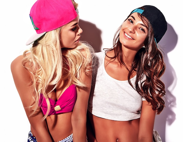 Fasonuje pięknych młodych brunetek i blondynów modelów w rnb stylu odziewa z różową kolorową baseball nakrętką odizolowywającą na bielu