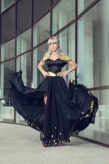 Fasonuje plenerową fotografię piękna zmysłowa kobieta z długimi włosami w luksusowej cekinowej sukni pozuje w lata miasteczku