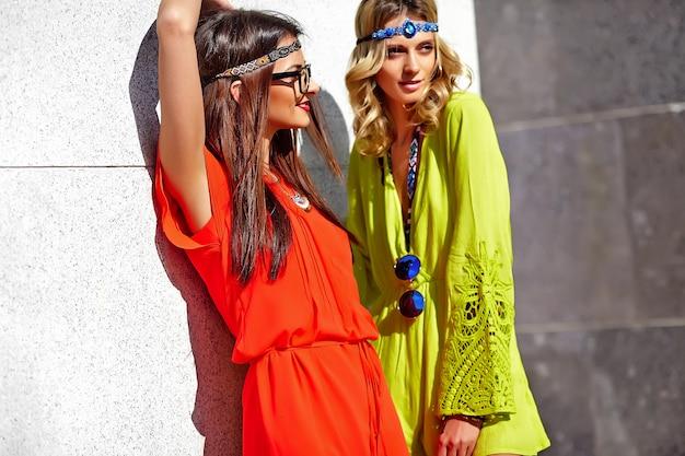 Fasonuje portret dwa młodego hipisa kobiety modeluje w letnim słonecznym dniu w jaskrawym kolorowym modnisiu odziewa