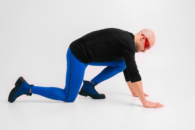 Fasonuje portret elegancki mężczyzna w błękitnych rajstopy i buty rozciąga i ćwiczy.