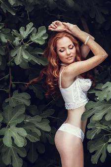 Fasonuje portret młoda piękna seksowna kobieta z długim falistym czerwonym włosy. ładna dziewczyna w białym staniku lub bieliźnie w letnim ogrodzie. portret moda w stonowanych kolorach.