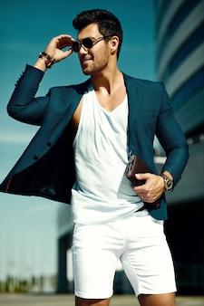 Fasonuje portret młodego seksownego biznesmena przystojnego modela mężczyzna w przypadkowym sukiennym kostiumu w okularach przeciwsłonecznych na ulicie