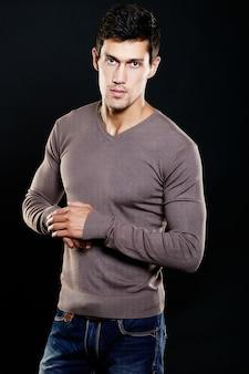 Fasonuje portret młody caucasian mężczyzna. przystojny model w przypadkowych ubraniach pozuje w studiu. atrakcyjny mężczyzna