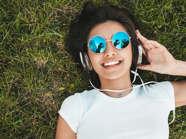 Fasonuje portret młody elegancki modniś kobiety lying on the beach na trawie w parku. dziewczyna jest ubranym modnego strój. uśmiechnięty model cieszy się jej weekendy. kobieta słuchanie muzyki przez słuchawki. widok z góry