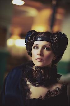 Fasonuje portret piękna brunetka w długiej sukni w budynku stary dworzec. kreatywny makijaż i fryzura
