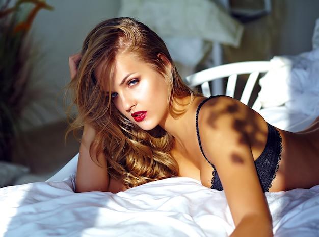 Fasonuje portret piękny seksowny młody dorosły blond kobieta model jest ubranym czarną erotyczną bieliznę kłama na łóżku przy zmierzchem