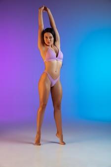 Fasonuje portret potomstwo dysponowana i sportowa kobieta w stylowym luksusowym stroju kąpielowym na gradiencie. idealne ciało gotowe na lato.