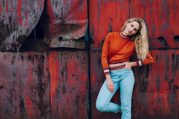 Fasonuje portret śliczna blondynki dziewczyna pozuje nad ośniedziałą kruszcową ścianą