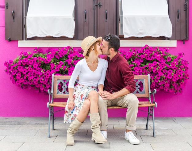 Fasonuje romantycznej pary całowanie siedzi na ławce. fioletowy kolor tła.