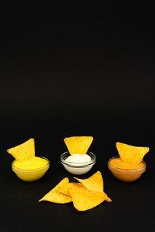 Fast food chipsy nachos z różnymi sosami na czarnym tle z miejscem na tekst