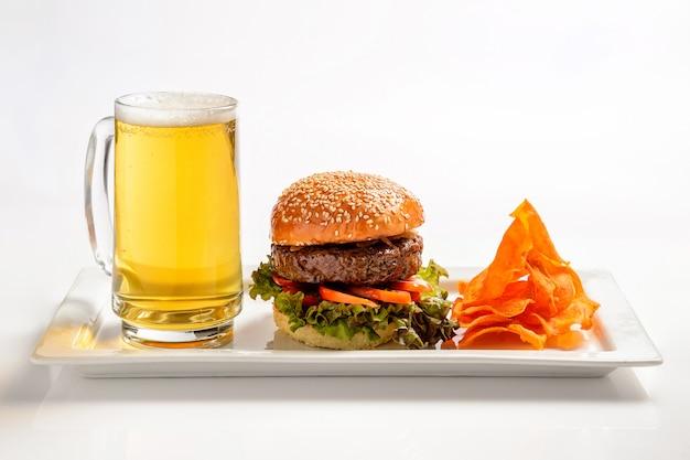 Fast food. duży burger z wołowiną i szklanką piwa.
