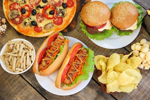 Fast food na starym drewnianym stole. pojęcie fast foodów. widok z góry. leżał na płasko.