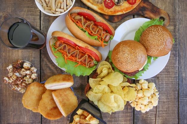 Fast food na starym drewnianym tle. pojęcie śmieciowego jedzenia. widok z góry. leżał płasko.
