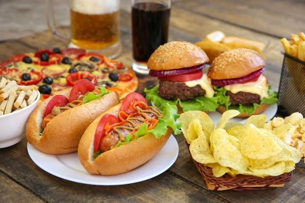 Fast food na starym drewnianym tle. pojęcie śmieciowego jedzenia.