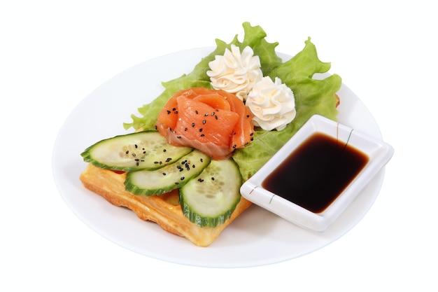 Fast food na talerzu, wafel belgijski, sałata, rozety masła, sos sojowy miska, plasterki ogórka, na białym tle obraz na białym tle.