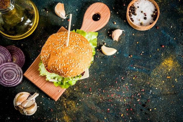 Fast food. niezdrowe jedzenie. pyszny świeży smaczny burger z kotletem wołowym, świeżymi warzywami i serem