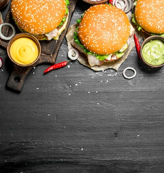 Fast food. różne burgery z sosami. na czarnej tablicy.