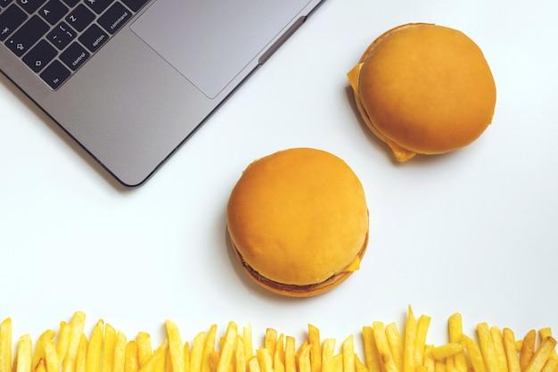 Fast food w pracy przekąski. laptop, hamburger i francuski smażyć w miejscu pracy.