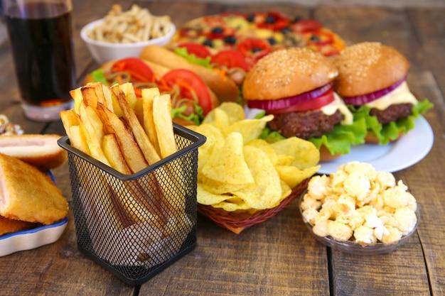 Fast foody na starym drewnianym tle. pojęcie fast foodów.