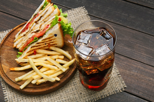 Fast foody w barze kanapkowym. kanapka z kurczakiem i warzywami, chipsy ziemniaczane i szklanka napoju cola z lodem na drewnie.