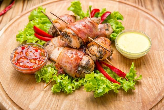 Faszerowana pierś kurczaka owinięta bekonem na talerzu z bliska. poziomy
