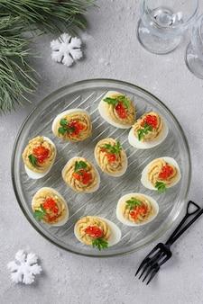 Faszerowane jajka z tuńczykiem i serem zdobione czerwonym kawiorem, świąteczna przekąska na jasnoszarym tle.
