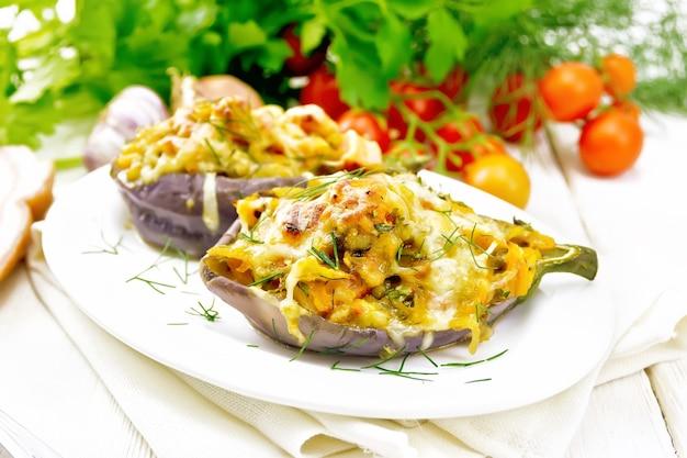 Faszerowany bakłażan z wędzonym mostkiem, pomidorami, cebulą, marchewką z czosnkiem, serem i ziołami w talerzu na ręczniku kuchennym na tle jasnej drewnianej deski