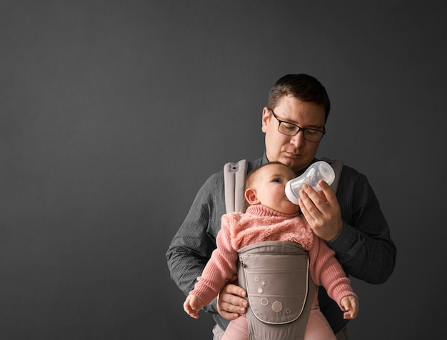 Fathre i jego dziecko w nosidełku na szarym tle ściany, dziecko ubrane w rodzicielstwo
