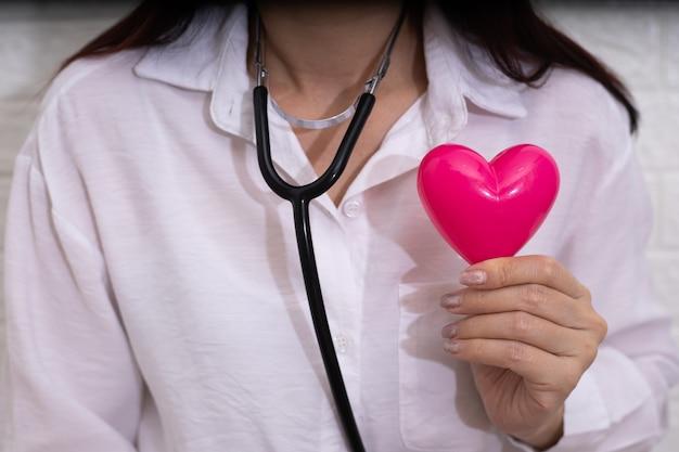 Feamle lekarz ze stetoskopem bada czerwone serce.