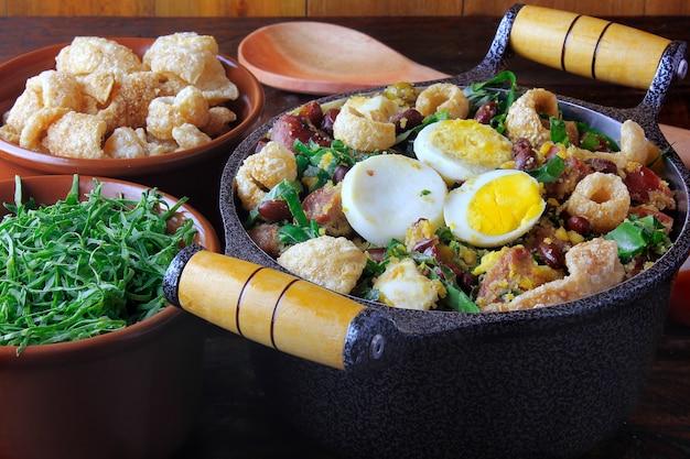 Feijao tropeiro typowe danie kuchni brazylijskiej, wykonane z fasoli, bekonu, kiełbasy, zieleniny, jajek, na rustykalnym drewnianym stole.
