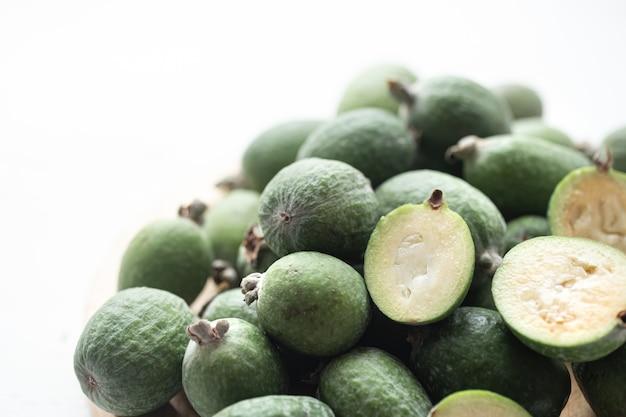 Feijoa zielony na jasnym tle. feijoa selloana to uprawa owoców z regionów tropikalnych. koncepcja zdrowej żywności ekologicznej, ekologiczne produkty naturalne, wegetariańskie, surowe produkty.